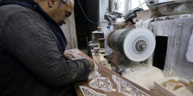 Un artisan incruste de nacre un panneau de bois, dans son atelier à Damas, le 1er décembre