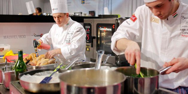Gabor Molnar of Hungary, left, prepares food with his assistant Adam Pohner, right, during