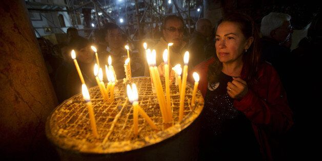 A Christian worshipper lights a candle at the Church of the Nativity, where Christians believe Jesus...