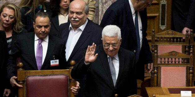 Palestinian President Mahmoud Abbas, waves to Greek lawmakers during his arrival at the Greek parliament...