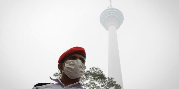 A security man stands guard in front of the Kuala Lumpur Tower shrouded by haze in Kuala Lumpur, Malaysia...