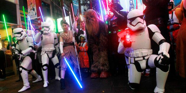 Fans dressed as Star Wars characters parade outside a movie theater