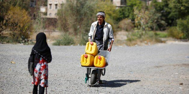A man pushes a cart loaded buckets to fill with water from a public tap amid an acute shortage of water,...