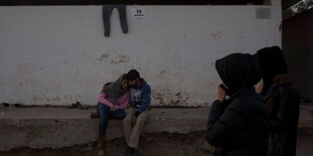A young couple embraces outside a registration center for migrants and refugees in Moria village on the...