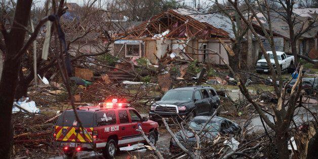 An emergency vehicle drives through a neighborhood in Rowlett, Texas, Sunday, Dec. 27, 2015, the morning...