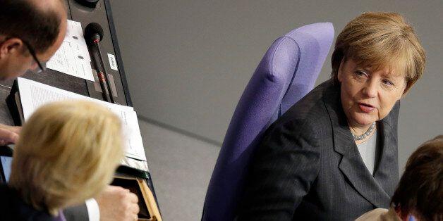 German Chancellor Angela Merkel, right, talks to German Defense Minister Ursula von der Leyen, front...
