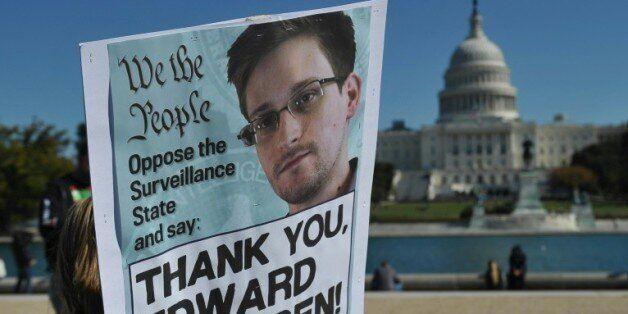 Des manifestants brandissent une affiche en soutien à Edward Snowden à Washington le 26 octobre