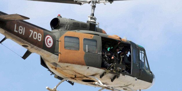 A Tunisian army helicopter flies over the Bardo museum, Wednesday, March 18, 2015 in Tunis, after gunmen...