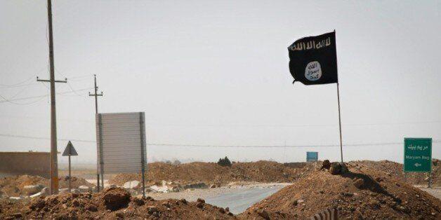 Un drapeau du groupe Etat islamique flotte le 11 septembre 2014 à Rashad, en