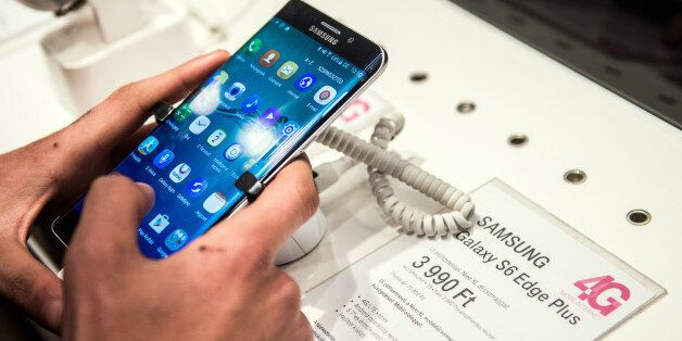 A customer browses a Samsung Electronics Co. Galaxy S6 Edge smartphone at a T-Mobile store, operated...
