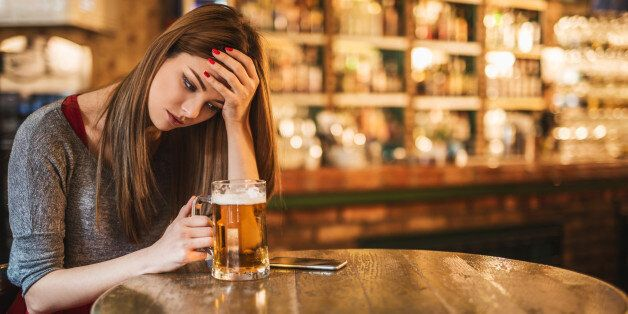 Pensive lonely young woman holding a glass of beer while sitting in a pub. She is looking at mobile phone...