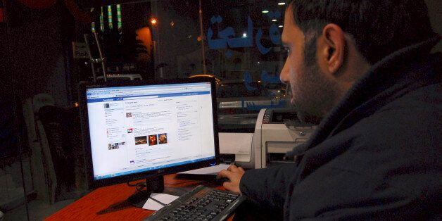 A Syrian man connects on his Facebook account at an internet cafe, in Damascus, Syria, on Tuesday Feb....