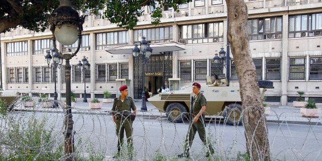 Tunisian soldiers walk around in front of Tunisian Interior Minister in Tunis, Thursday Oct. 20, 2011....