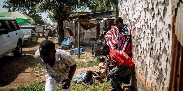 Des hommes se mettent à l'abri pendant que des tirs à l'arme lourde retentissent à Bangui, le 13 décembre