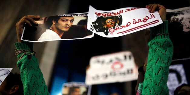 An Egyptian journalist holds posters calling for the release of photojournalists Mohammad al-Batawi,...