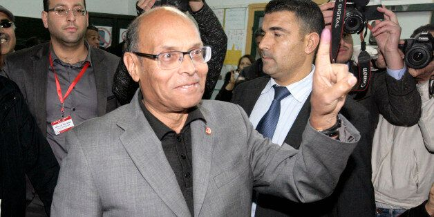 Tunisia's outgoing President, Moncef Marzouki, displays the indelible ink mark on his finger after voting...