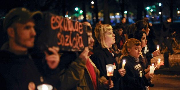 Youth demonstrators hold lit candles simulating a burial during a general strike against government austerity...