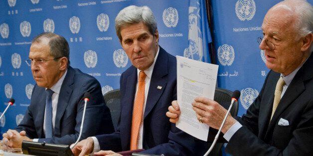 U.N. Special Envoy for Syria Staffan de Mistura, right, shows a copy of a Security Council resolution...