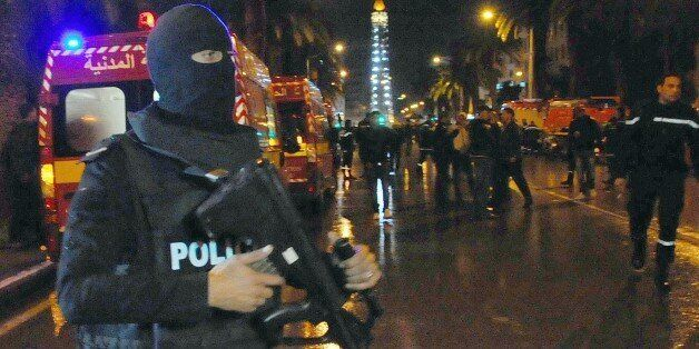 A hooded police officer prevents media from aproaching the scene of a bus explosion in the center of...