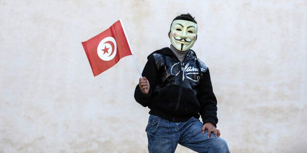 A civilian wearing a mask holds a Tunisian flag in Sidi Bouzid, central Tunisia, Tuesday, Dec. 17, 2013...
