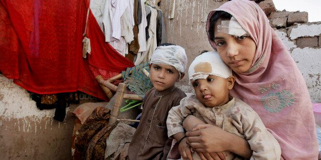Pakistani children sit in the rubble of their home damaged from an earthquake in Peshawar, Pakistan,...