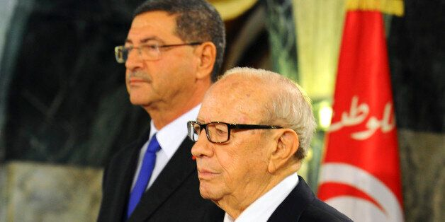 Tunisian President Beji Caid Essebsi, front and new Prime Minister Habib Essid stand at attention during...