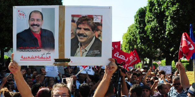 A Tunisian demonstrator holds a poster of slain politicians, lawyer and secular politician Chokri Belaid,...