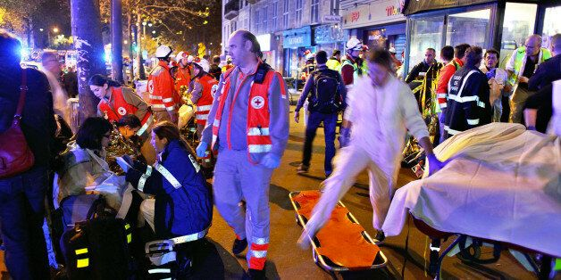 People rest on a bench after being evacuated from the Bataclan theater after a shooting in Paris, Saturday,...