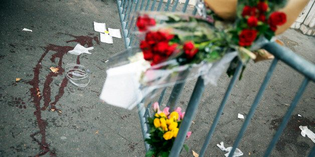 Flowers are placed outside the Bataclan concert hall, Saturday, Nov. 14, 2015 in Paris. French President...