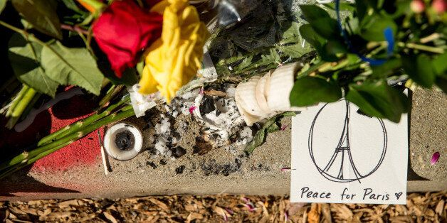 Mourners leave flowers and cards outside the gates of the French Embassy in Washington, Sunday, Nov....