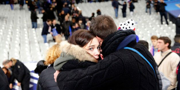 Spectators embrace each other as they stand on the playing field of the Stade de France stadium at the...