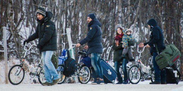 Des réfugiés en byciclette traverssent la frontière russo-norvégienne près de Kirkenes le 12 novembre