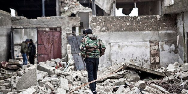 Free Syrian Army fighters walk amid the ruins of a village situated a short distance from an area where...