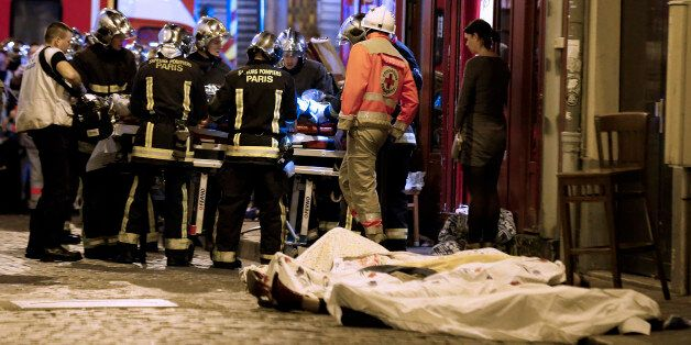 Rescue workers gather at victims in the 10th district of Paris, Friday, Nov. 13, 2015. Several dozen...