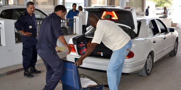 Tunisian custom officers check the luggage of a man fleeing from Libya at the Ras Ajdir border post between...