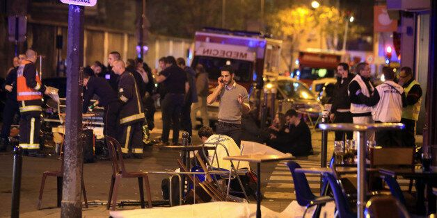 Victims lay on the pavement in a Paris restaurant, Friday, Nov. 13, 2015. Well over 100 people were killed...