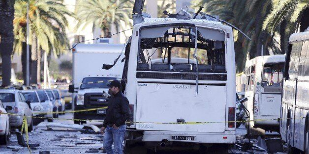 A man walks past the bus that exploded Tuesday in Tunis, Wednesday Nov.25, 2015. Tunisia's president...