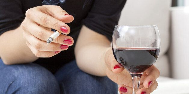 Young woman addicted to cigarettes and alcohol sitting by the table at