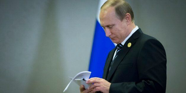 FILE - In this Monday, Nov. 16, 2015 file photo, Russian President Vladimir Putin reads his notes waiting...