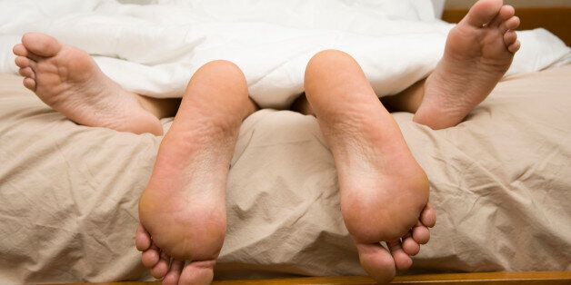 View of feet of couple having sex in