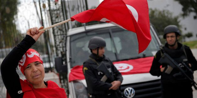 A woman waves the Tunisian flag as policemen stand guard at the National Bardo Museum two days after...