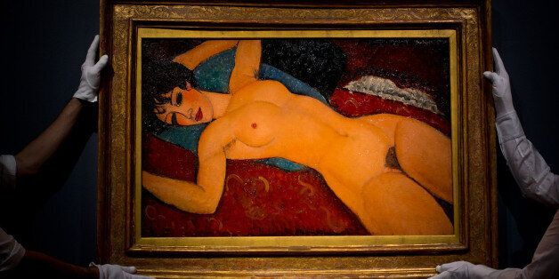 LONDON, ENGLAND - OCTOBER 09: Art handlers hang the painting 'Nu couche' by artist Amedeo Modigliani...