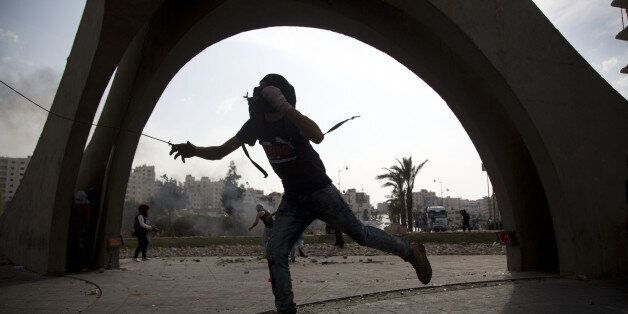 A Palestinian hurls a stone during clashes with Israeli troops, near Ramallah, West Bank, Tuesday, Oct....