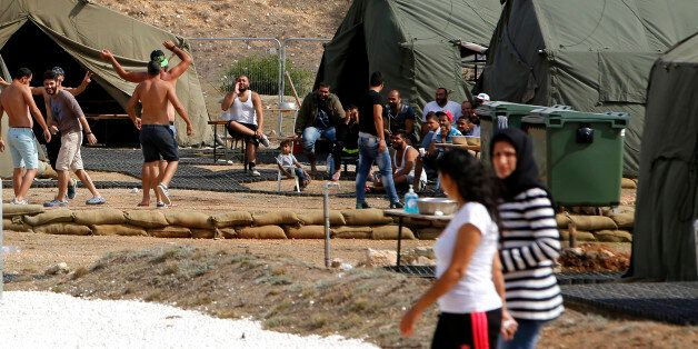 Migrants are seen at the temporary transit facility in Dhekelia Garrison, a British military base on...