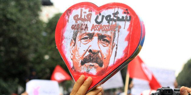Demonstrators hold a poster showing slain opposition leader Chokri Belaid with written in arabic and