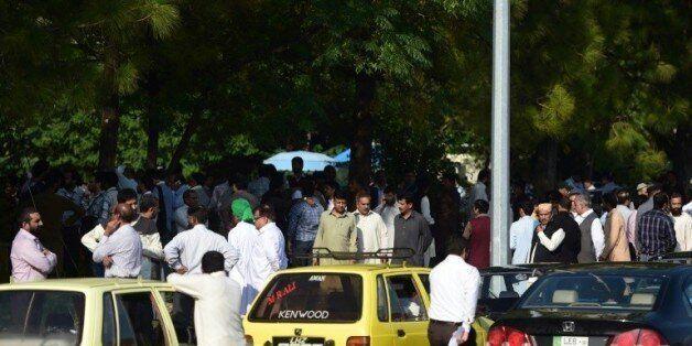 Des personnes attendent dans la rue après des secousses sismiques importantes, le 26 octobre 2015 à Islamabad,...