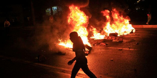 A masked protester runs past garbage bins set on fire by supporters of the pro-Kurdish Peoples's Democratic...