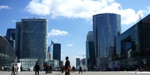 People walk in La Defense business district, west of Paris, Wednesday, April 9, 2014. La Défense is...