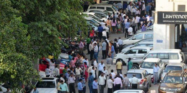 Des personnes attendent dans la rue, après des secousses sismiques ressenties à New Delhi, le 26 octobre...