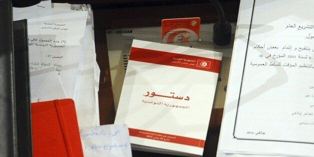 A copy of the new Tunisian Constitution lays on a parliament member's desk at the Constituent Assembly,...